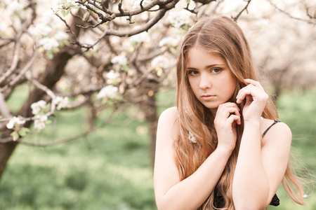 Beautiful blonde girl 14-16 year old posing in pear orchard. Springtime.  Stock Photo