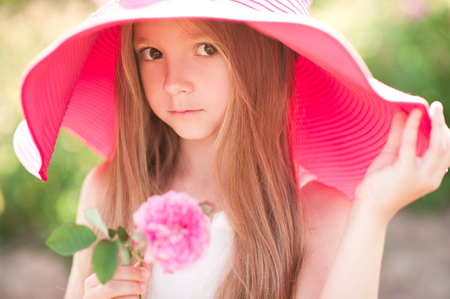 かわいい赤ちゃん女の子 4 5 歳身に着けている大きなピンクの帽子屋外の花を保持します。カメラを見ています。夏の時間。子供の頃。
