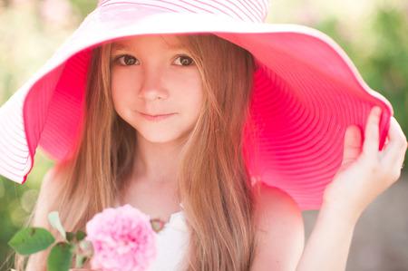 アウトドア ローズ金髪子供女の子 4 5 歳身に着けている大きなピンクの帽子持株を笑顔します。カメラを見ています。子供の頃。夏の時間。