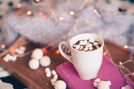 Cup of coffee with marshmallow staying on book with candies on wooden tray in room. Christmas time. Winter season.  Stock Photo