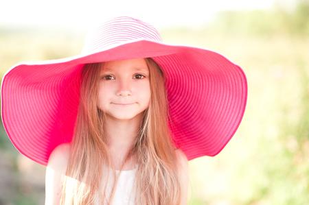 4-5 歳屋外大きな帽子をかぶって笑顔の女の子.カメラを見ています。子供の頃。 写真素材