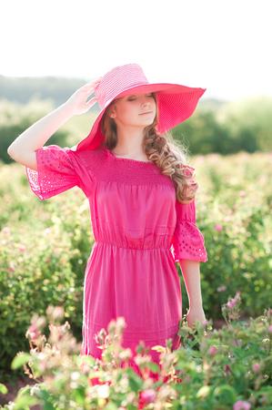 十代の少女 14-16 歳の身に着けているピンクのドレスと帽子のバラのフィールドに立って笑っています。夏の時間。