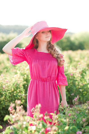 Smiling teen girl 14-16 year old wearing pink dress and hat standing in rose field. Summer time.