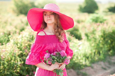 Smiling teenage girl 14-16 year old wearing pink dress and hat holding roses outdoors. Looking away. Summer time.  Stock Photo