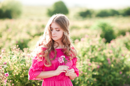 Beautiful blonde teen girl 14-16 year old wearing pink dress holding rose flower outdoors. Summer portrait.