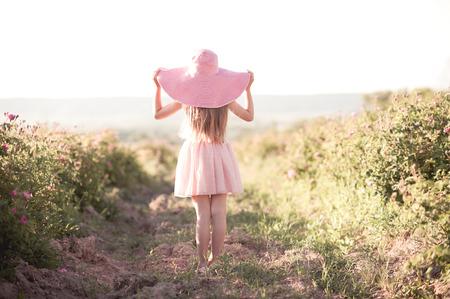 子供女の子 4-5 歳着用ドレスと大きな帽子に立ってバラ フィールド。夏の時間。子供の頃。