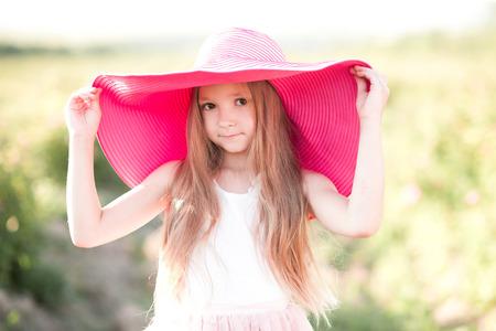 かわいい赤ちゃん女の子 4 5 歳身に着けている大きなピンクの帽子アウトドア。カメラを見ています。子供の頃。夏の時間。