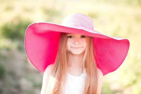 面白い笑顔子供女の子 4 5 歳身に着けている大きなピンクの帽子屋外。カメラを見ています。子供の頃。 写真素材
