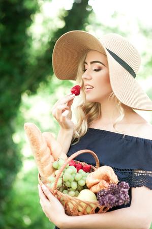 食物と一緒にイチゴ持株バスケットを食べて美しいブロンドの女の子: 焼きたてのパン、ブドウ、ベリー屋外。健康的な食事。20 代。