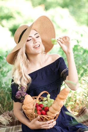 微笑んでいる女の子 24 29 歳公園でピクニックを持ちます。籐のバスケットに果物やパンを保持します。屋外、麦藁帽子とスタイリッシュなブルーの