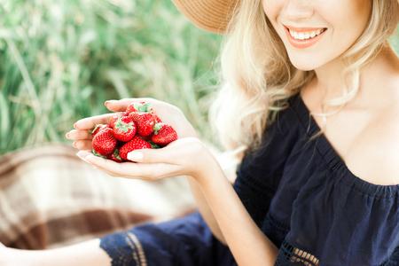 屋外をすぐ手で女の子持株イチゴを笑っています。健康的な食事。