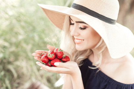 金髪女性 24 26 歳持株イチゴ屋外を笑っています。麦わら帽子をかぶっています。健康的な食事。20 代。 写真素材