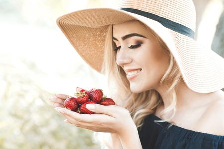 イチゴを押し、晴れた日の屋外麦わら帽子を着ている金髪の女性が微笑んでいます。健康的な食事。夏のシーズン。
