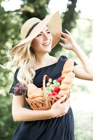新鮮な金髪女性 24 29 歳の身に着けている青いドレスとフルーツ バスケットを保持している麦わら帽子の笑みを浮かべて、屋外パンします。楽しみに