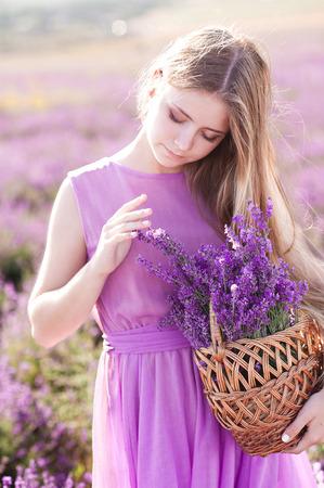 美しいブロンドの女の子 14-16 歳持株バスケット フィールドでラベンダーの花を持つ。屋外でポーズかわいい女の子。夏の時間。