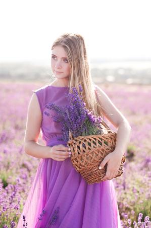 美しいブロンドの女の子 14-16 歳持株バスケット フィールドでラベンダーの花を持つ。屋外ポーズ紫色のドレスを着ています。