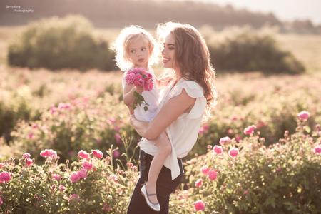 ローズ フィールドで 3-4 歳の女の赤ちゃんを持つ女性。夏のシーズン。母性。家族との時間。 写真素材