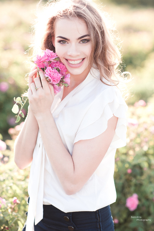 Smiling blonde girl 14-19 year old holding roses in field. Looking at camera. Summer time.