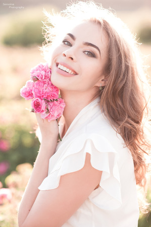 金髪の女の子 24 29 歳持株バラ屋外を笑っています。カメラを見ています。20 代、夏シーズン。