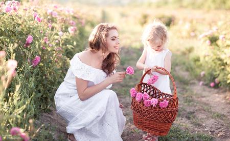 屋外のバスケットの子供女の子集めてバラで笑顔の女性。母性。マタニティ。家族との時間。 写真素材