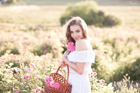 金髪の美しい少女 2 29 歳 wearig ホワイト ドレス持株バスケット ローズ フィールドのバラで。カメラを見ています。20 代。