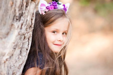 赤ちゃん女の子 4 5 歳屋外ポーズ笑顔。カメラを見ています。手作りカチューシャを着用します。子供の頃。