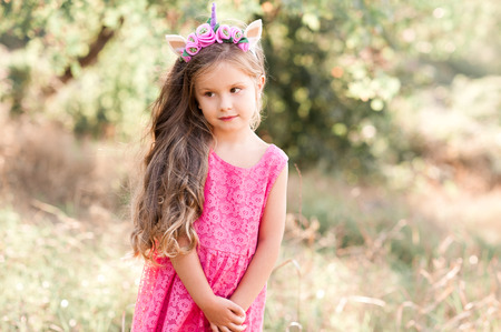 Cute baby girl 4-5 year old wearing stylish dress and headband outdoors. Childhood. Summer time.