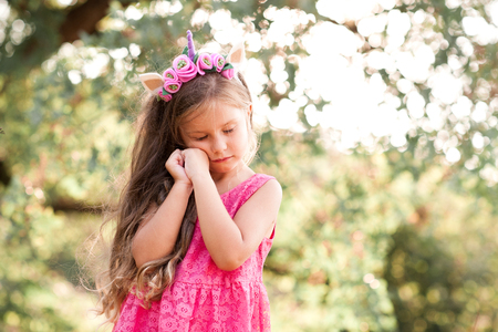 Pretty baby girl 4-5 year old posing with eyes closed outdoors. Wearing trendy dress.