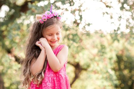 笑っている赤ちゃん女の子 4 5 歳目を閉じて屋外ポーズします。トレンディなドレスを着てください。