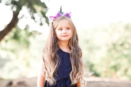 Schattige baby meisje 4-5 jaar oud dragen jurk en handgemaakte hoofdband buitenshuis. Wegkijken. Zomertijd.