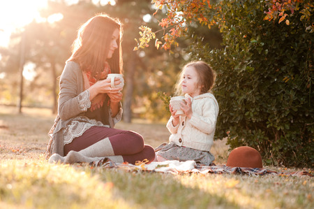 Mother drinking tea with kid daughter 4-5 year old  sitting in sun light in park. Wearing autumn knitted clothes. Looking at each other. Motherhood. Childhood.