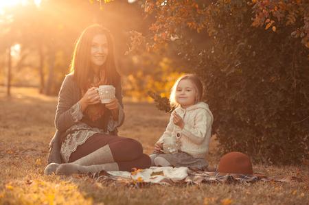 太陽の光の公園で 4-5 歳の娘と一緒にお茶を飲みながら母を笑っています。身に着けている保持カップのセーターを編んだ。カメラを見ています。母 写真素材