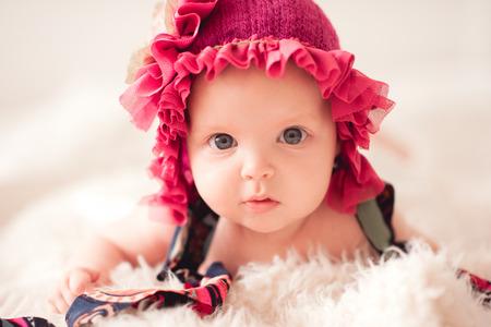かわいい女の子 2-3 ヶ月着用スタイリッシュな帽子フリル ベッドで横になっていると。カメラを見ています。子供の頃。