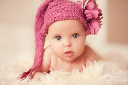 装飾花とピンクの帽子を編んだかわいい赤ちゃん女の子 2 ・ 3ヶ月着用します。を探しています。子供の頃。 写真素材