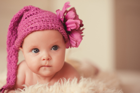 Funny baby girl 2-3 month old wearing pink knitted hat with decorative flower closeup. Lying in bed. Childhood.
