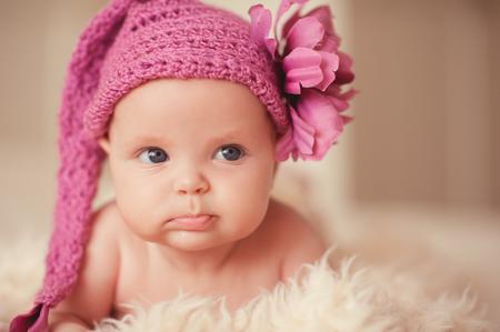 かわいい赤ちゃんおかしい 2-3 ヶ月を身に着けているピンク ニット帽子花のベッドで横になっていると。離れています。子供の頃。