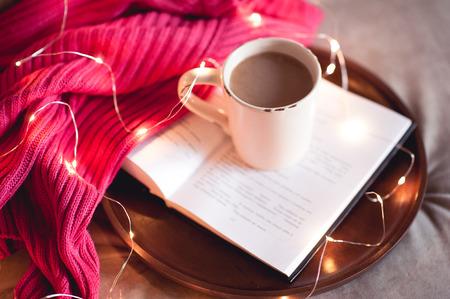 一杯のコーヒーは、ニットのセーターを着て、クリスマス ライトのラウンド木製トレイに開かれた本に滞在します。おはようございます。 写真素材