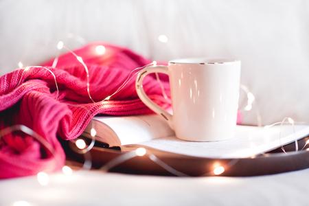 クローズ アップ ベッドの木製皿のニットのセーターを開いた本に滞在紅茶のカップ。おはようございます。朝食。