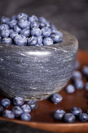 木製トレイのブルーベリーと大理石のボウルをクローズ アップ。健康的な食事。選択と集中。 写真素材
