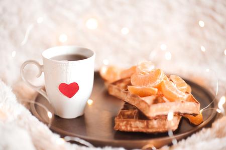 ワッフルとベッドの木製皿のオレンジ赤の心と、お茶を一杯。美味しい朝食。おはようございます。
