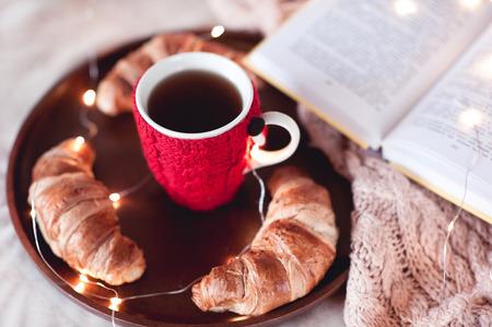 自家製クロワッサンとベッドの木製のトレイの上に開いた本黒茶杯、ニット。冬のシーズン。おはようございます。 写真素材