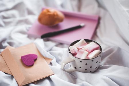 ベッドでコーヒー カップはラブレターし、背景にケーキで帳を開きます。おはようございます。選択と集中。