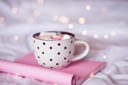 ベッドでのピンクのノートに泊まるクリスマス ライト クローズ アップ コーヒー杯、甘い。おはようございます。選択と集中。