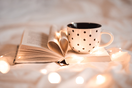 Open book with folded sheets in heart shape and cup of tea in bed with Christmas lights closeup. Good morning. Breakfast time.