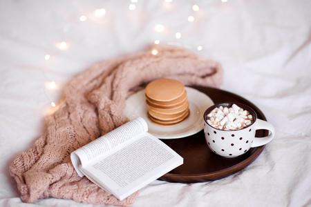 マシュマロ入りのコーヒーカップは、オープンブックとクリスマスライトの上にベッドでパンケーキと木製のトレイに滞在します。おはようござい 写真素材