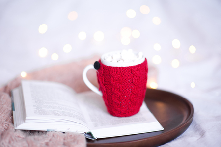 ニット一杯のクリスマス ライトで開かれた本にコーヒーをクローズ アップ。おはようございます。
