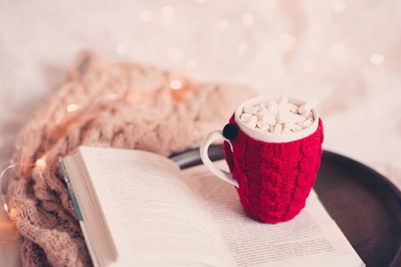 クリスマスライトのクローズアップの上にベッドにニットスカーフとオープンブック上のコーヒーのニットカップ。おはようございます。