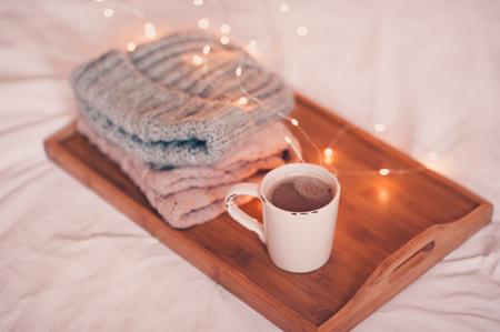 ニット帽子とスカーフで木製のトレイに滞在コーヒーのカップは、クリスマスライトの上にクローズアップ。おはようございます。冬。