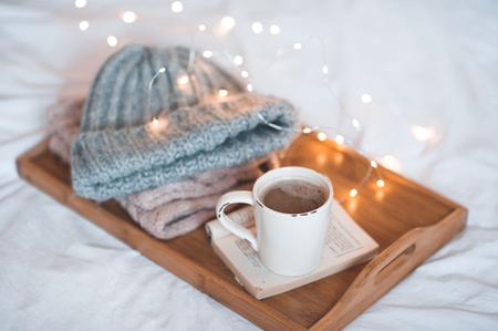 ニットウェアと木製のトレイの上に開かれた本のコーヒーのカップは、クリスマス ライトをクローズ アップ。おはようございます。冬のシーズン。