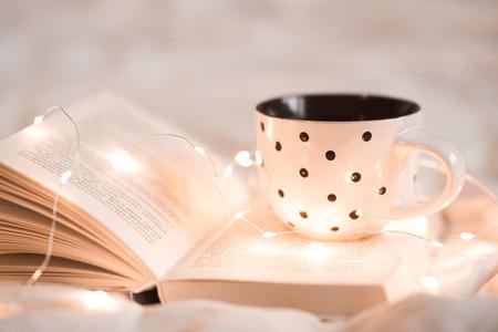 ベッドのクローズ アップのクリスマス ライトで開かれた本にティーのカップ。おはようございます。朝食の時間。